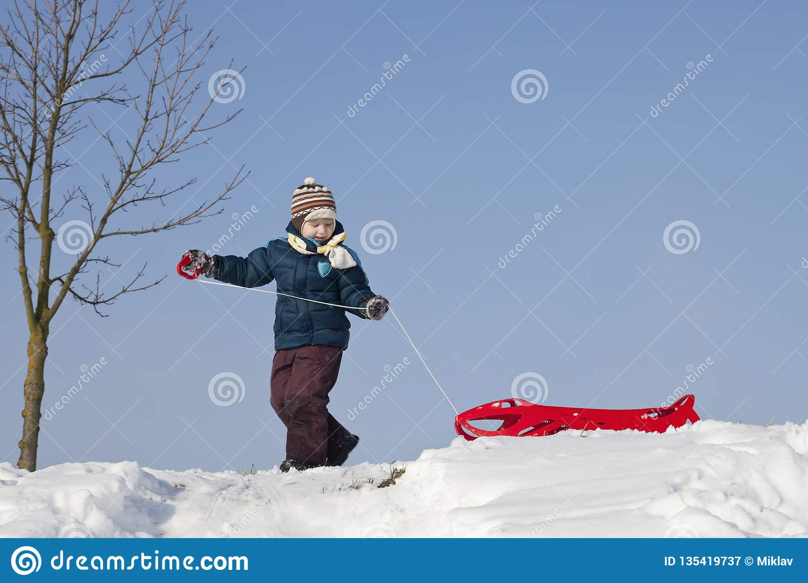 Boy with red plastic sledge on a snowy hill