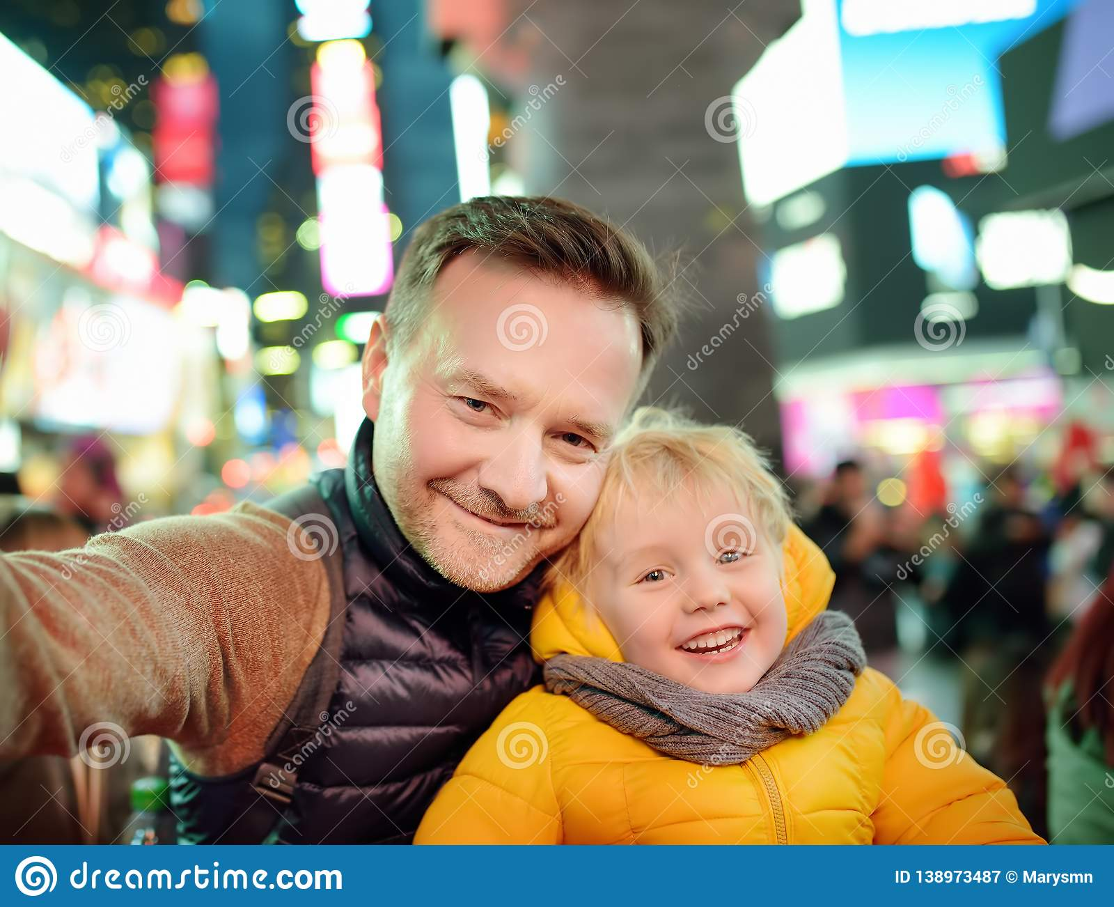 Little boy and his father taking selfie on Times Square in evening, downtown Manhattan