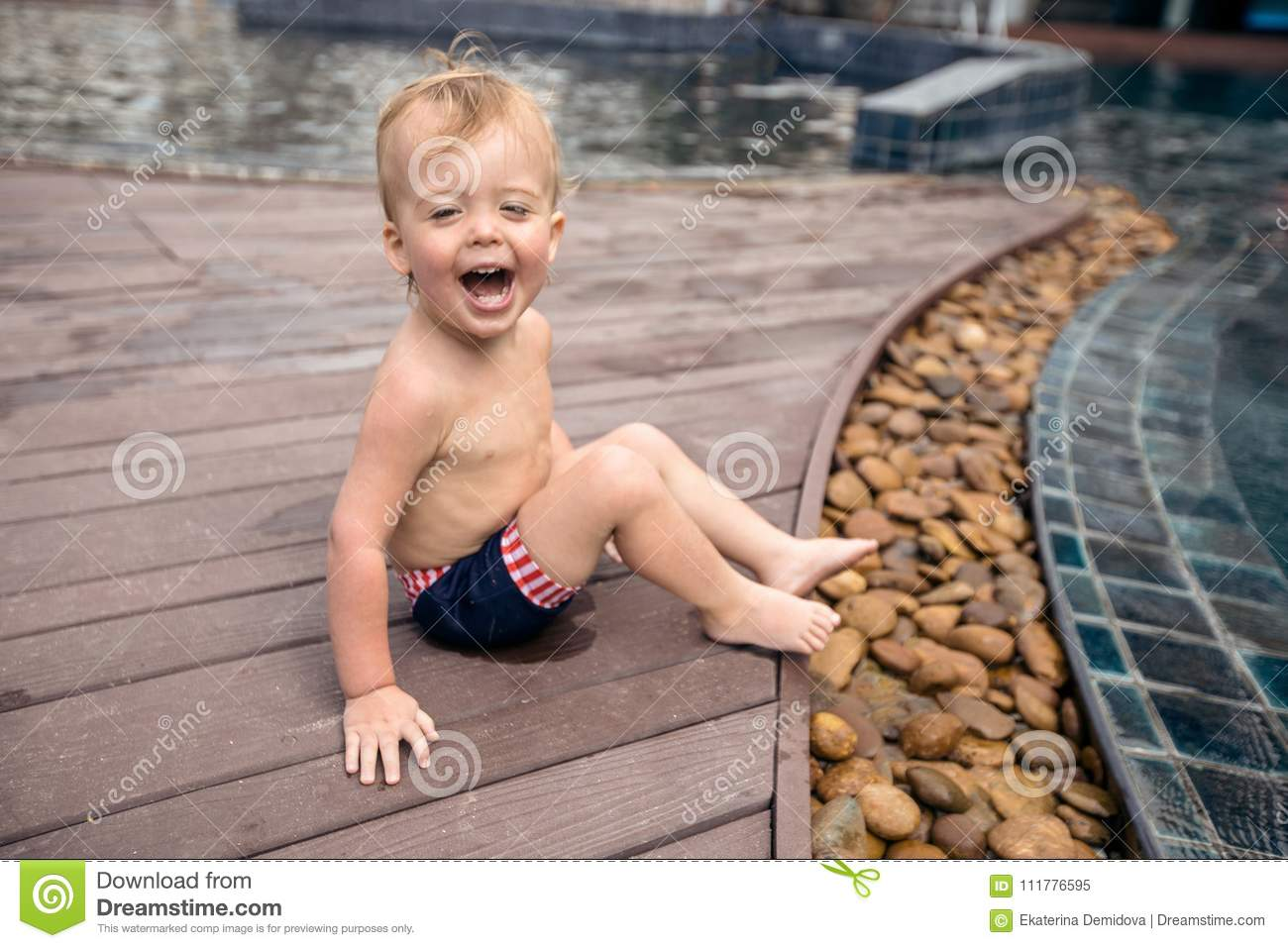 Little boy laughing on poolside