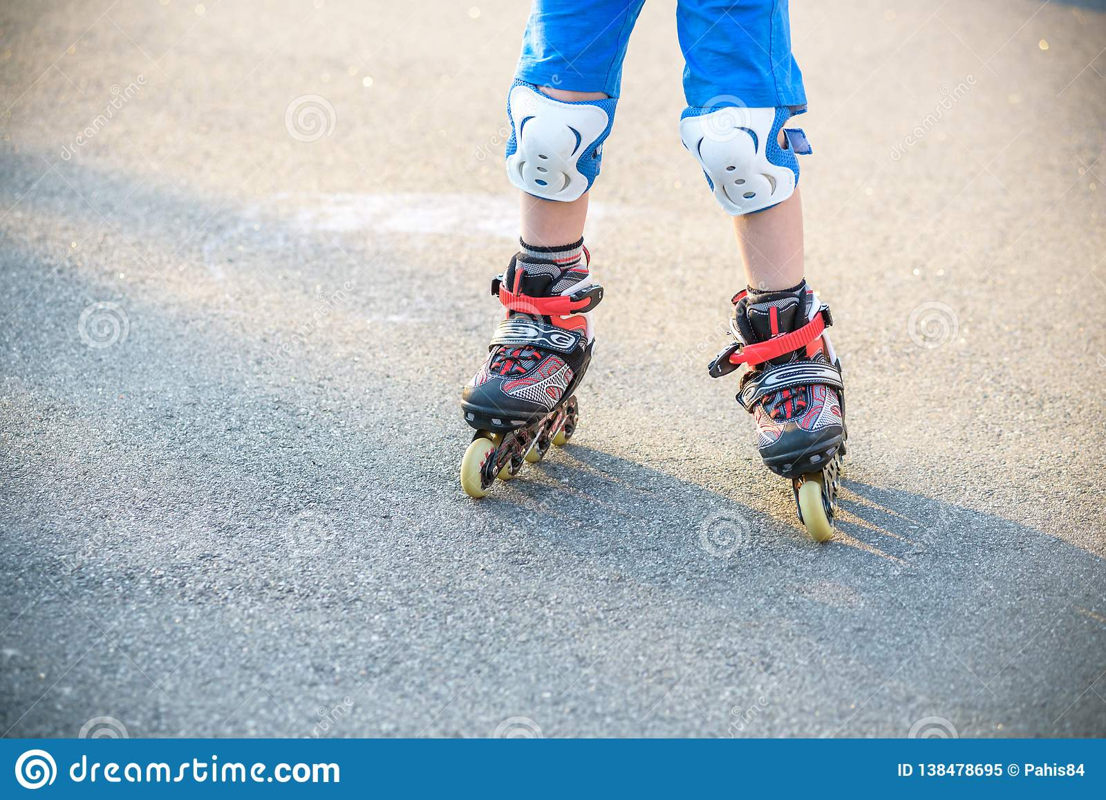 Little boy learning to roller skate in summer park. Children wearing protection pads for safe roller skating ride. Active outdoor