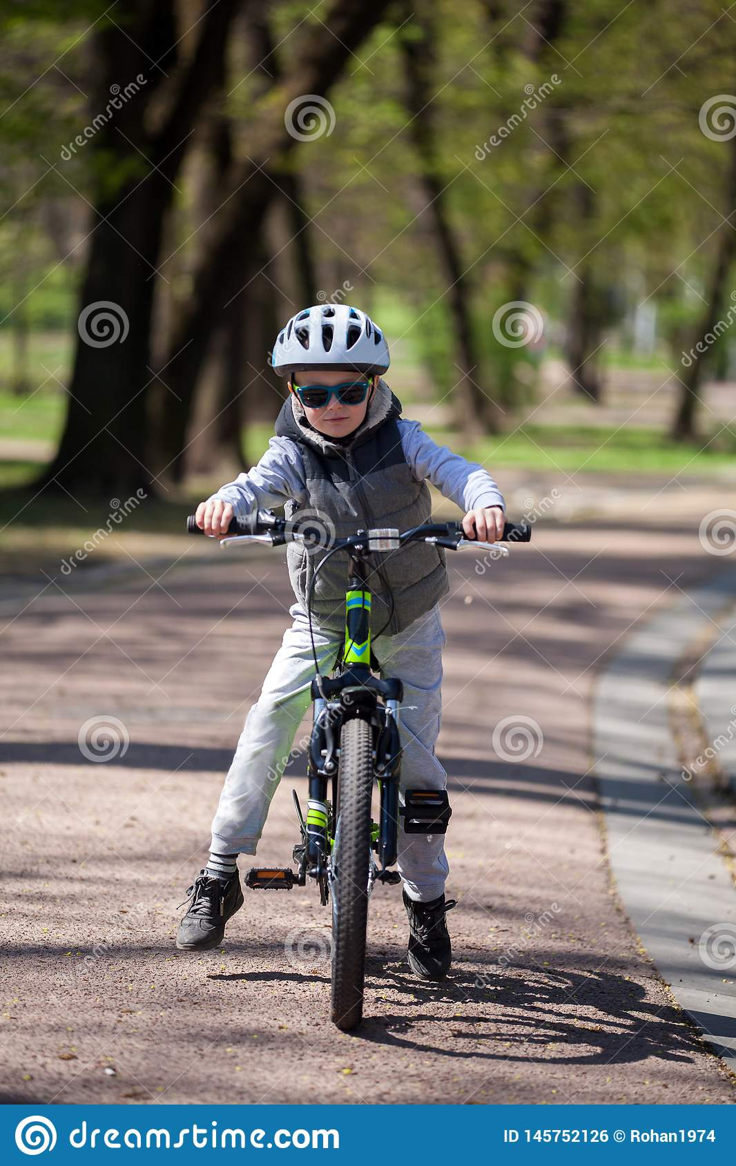 Little boy learns to ride a bike in the park. Cute boy in sunglasses rides a bike. Happy smiling child in helmet riding a cycling
