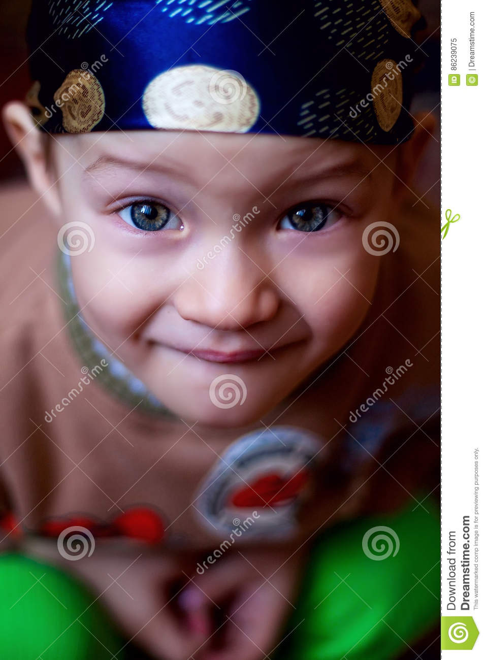 Little boy looking at the camera, blue eyes bright in the bandana