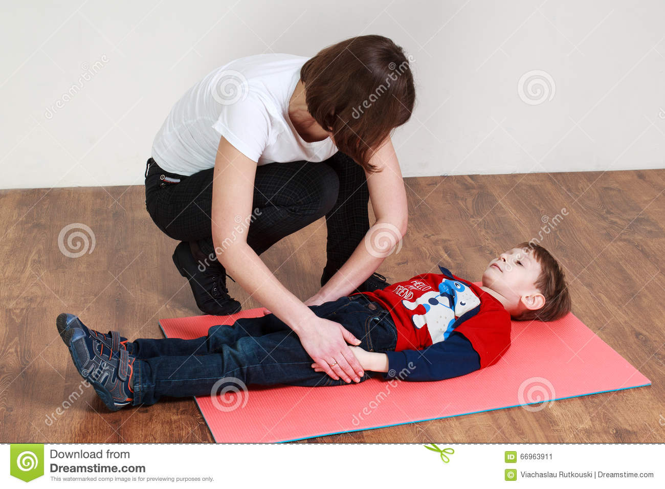 Little Boy Is Lying On The Mat At A Gym Trainer Is