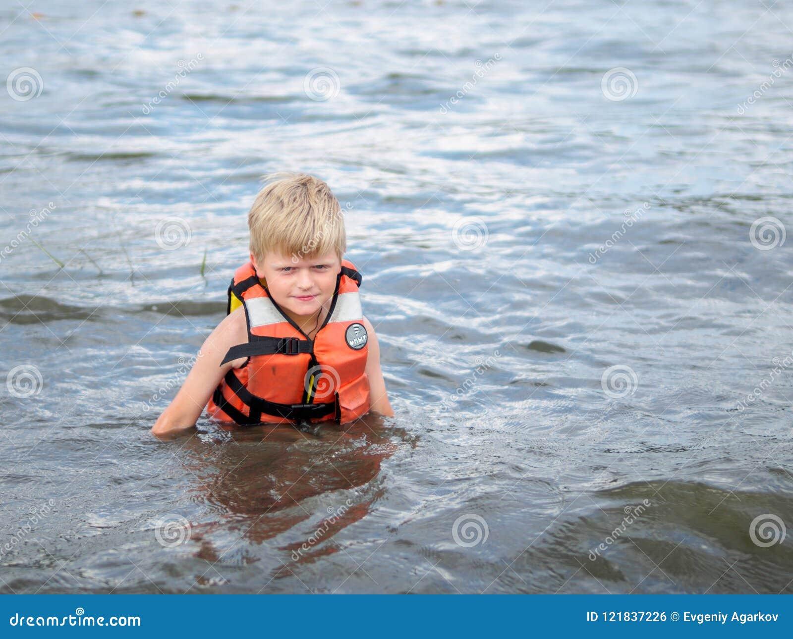 Cute little boy in orange life vest swimming in the river