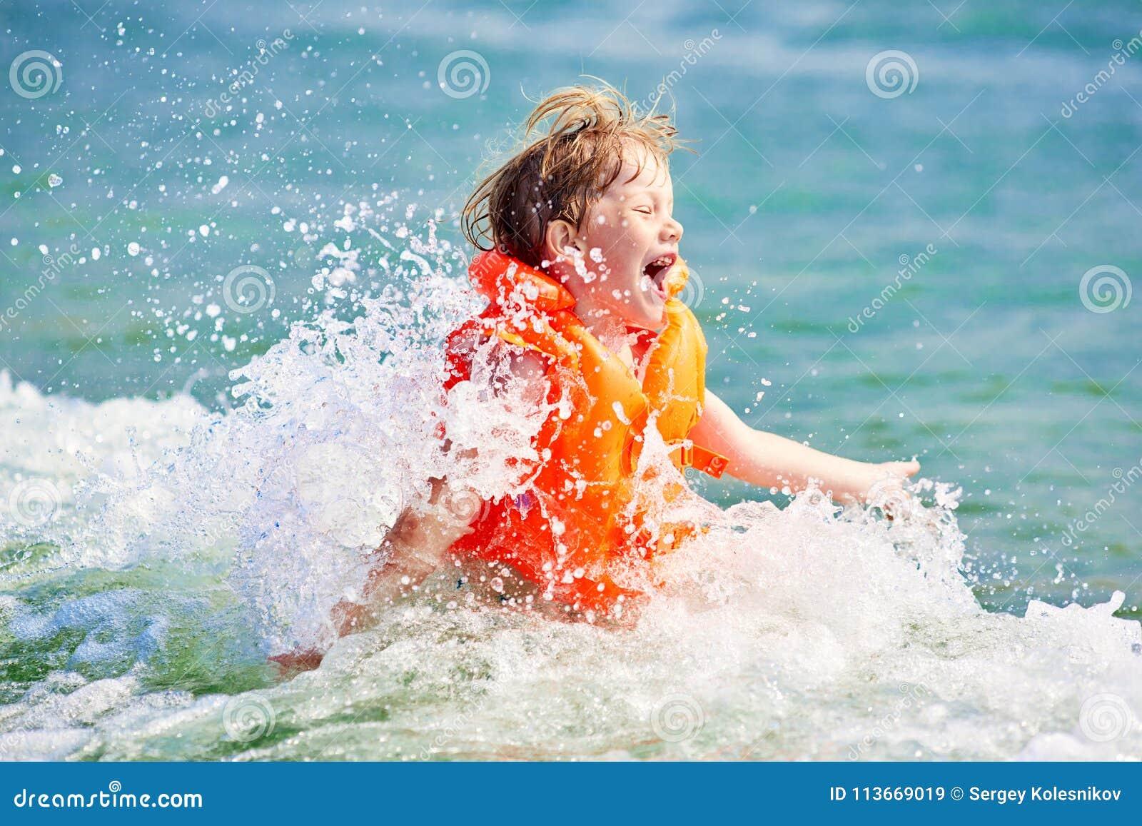 Little boy in orange life vest swimming in wave sea