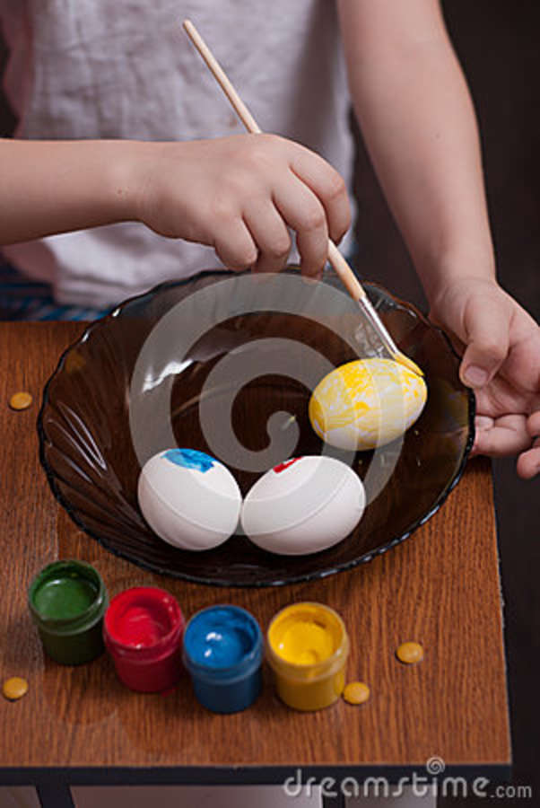 A little boy paints the eggs on the eve of Easter, colorful paints and brush,
