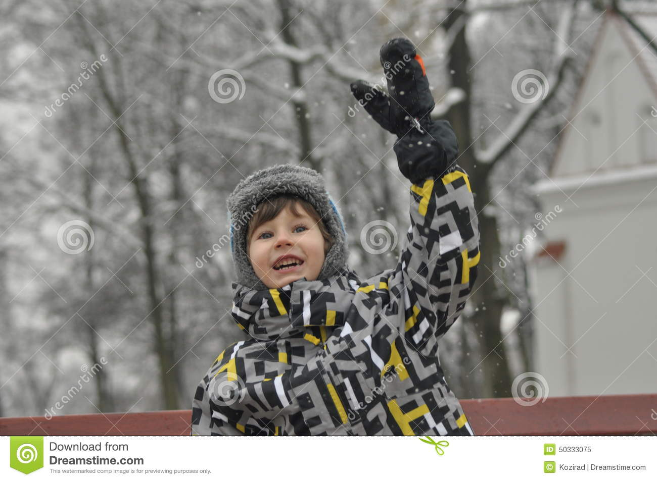 The little boy in the park in winter. Child in a cap and gloves.