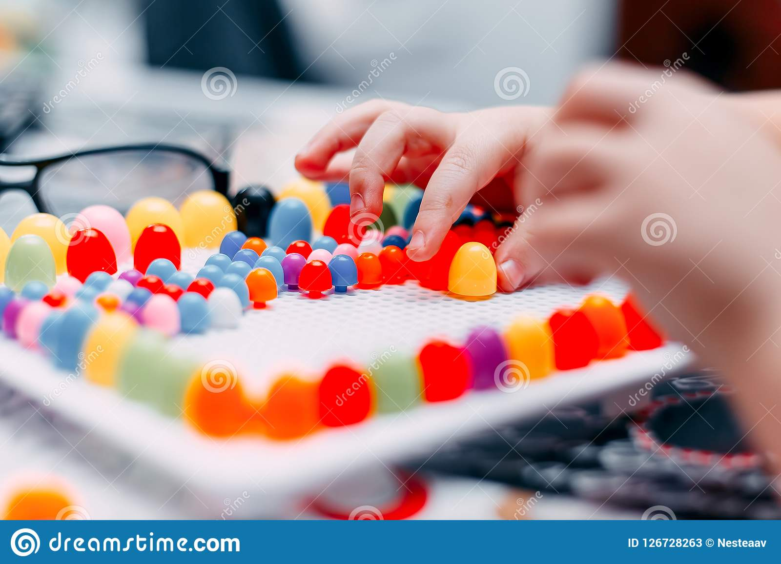 Little boy play board game on table mosaic colored. Game for fingers learn motoric Stock Photos