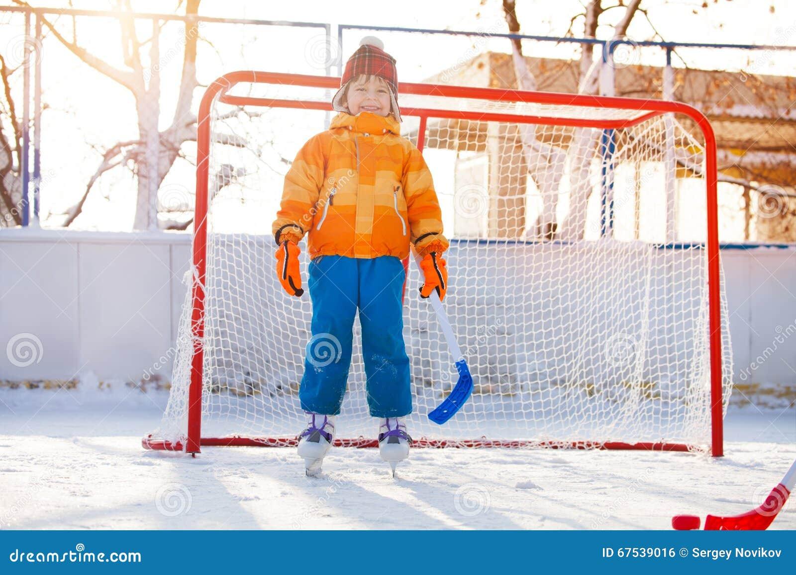 Little boy play hockey standing in gates