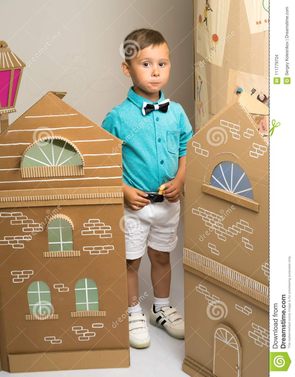A little boy is playing with colorful houses.