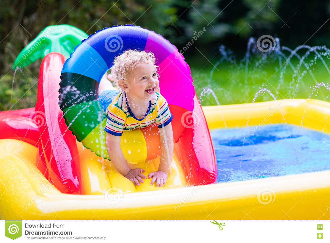 Little boy playing in garden swimming pool stock photo for Kids swimming pool garden