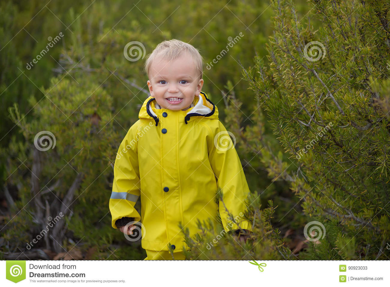 Little boy playing in rainy summer park. Child with colorful rainbow umbrella, waterproof coat and boots jumping in