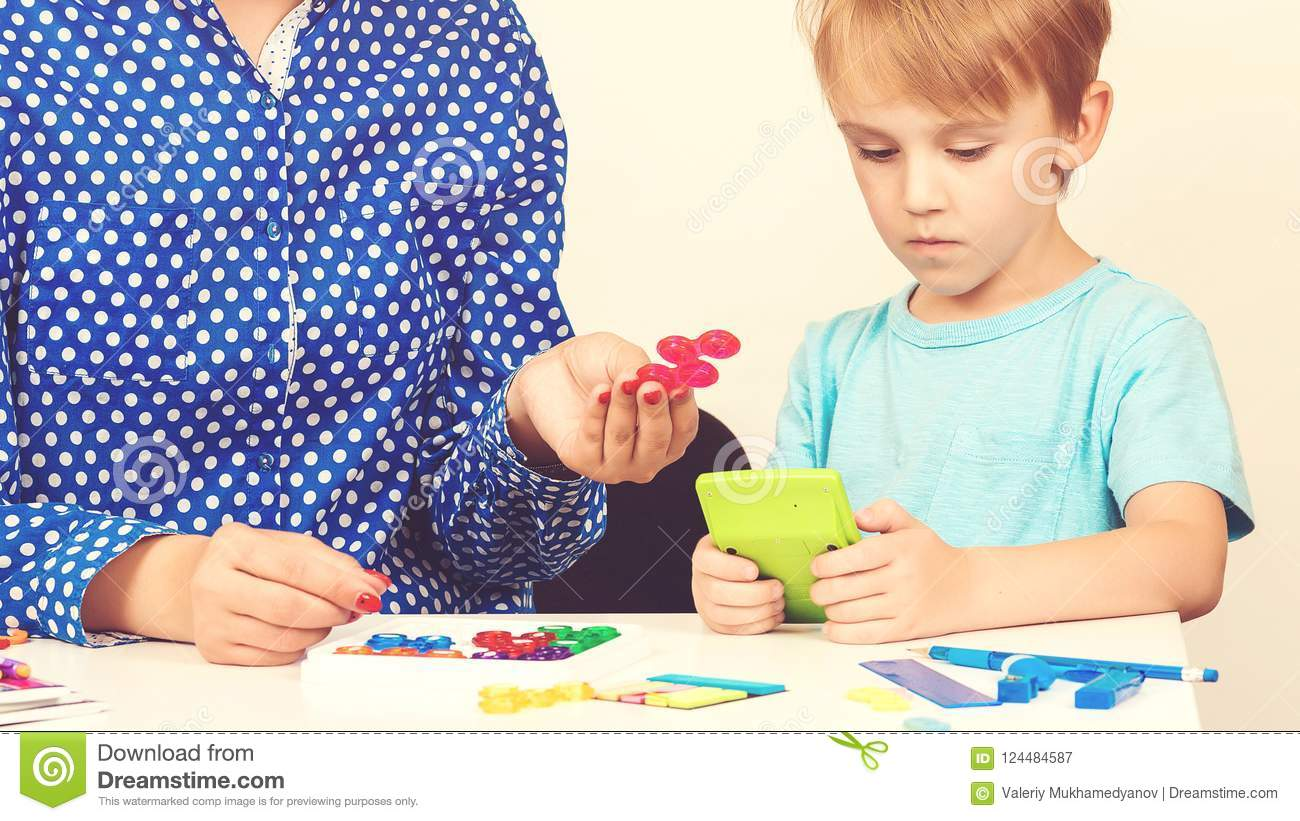 Little boy plays logical game at the lesson of a psychologist. Smart kid with teacher learning at preschool classroom. Education a