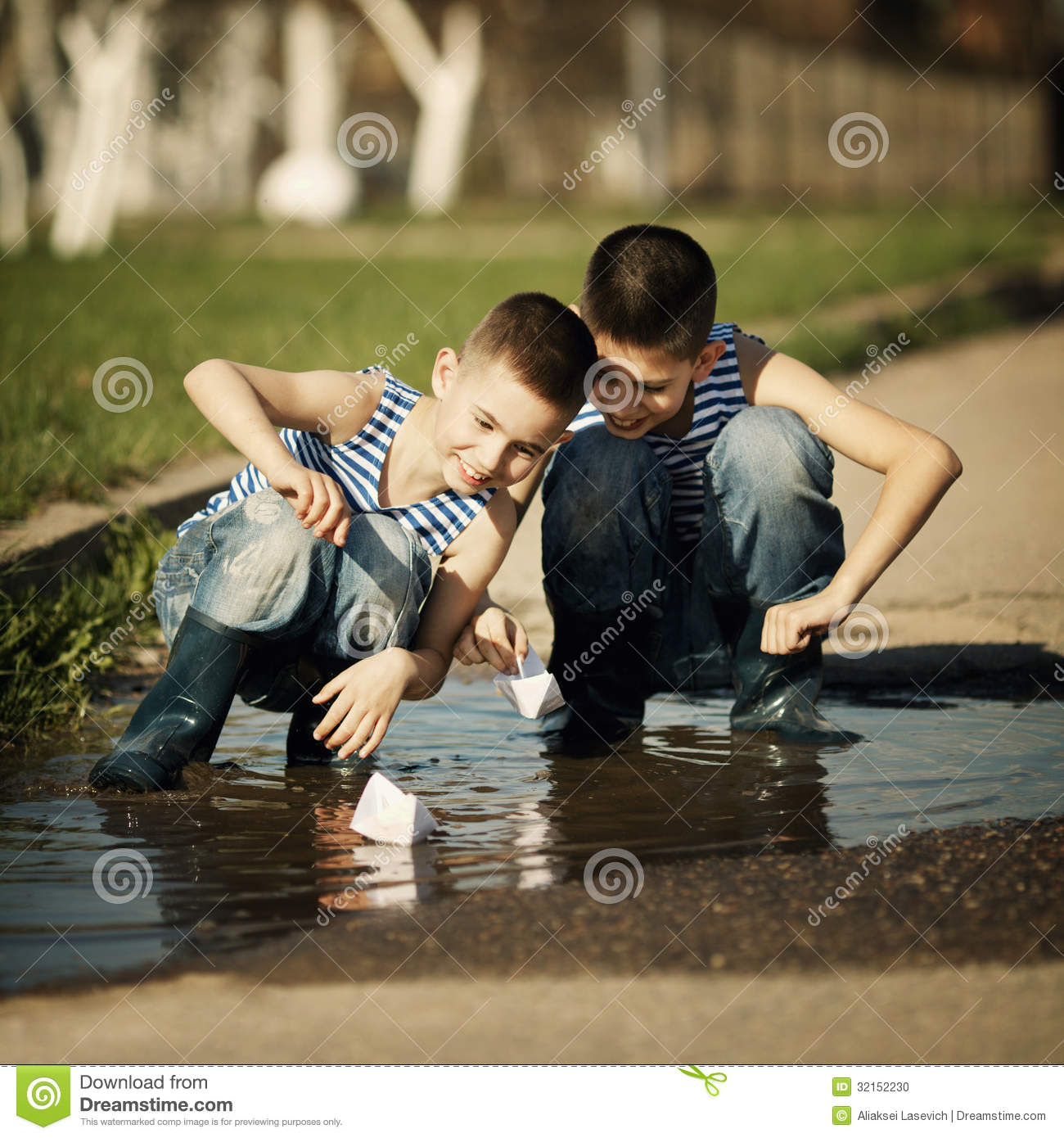 Lillle Boy Toys Boats : Little boy plays with paper boats in puddle stock photo