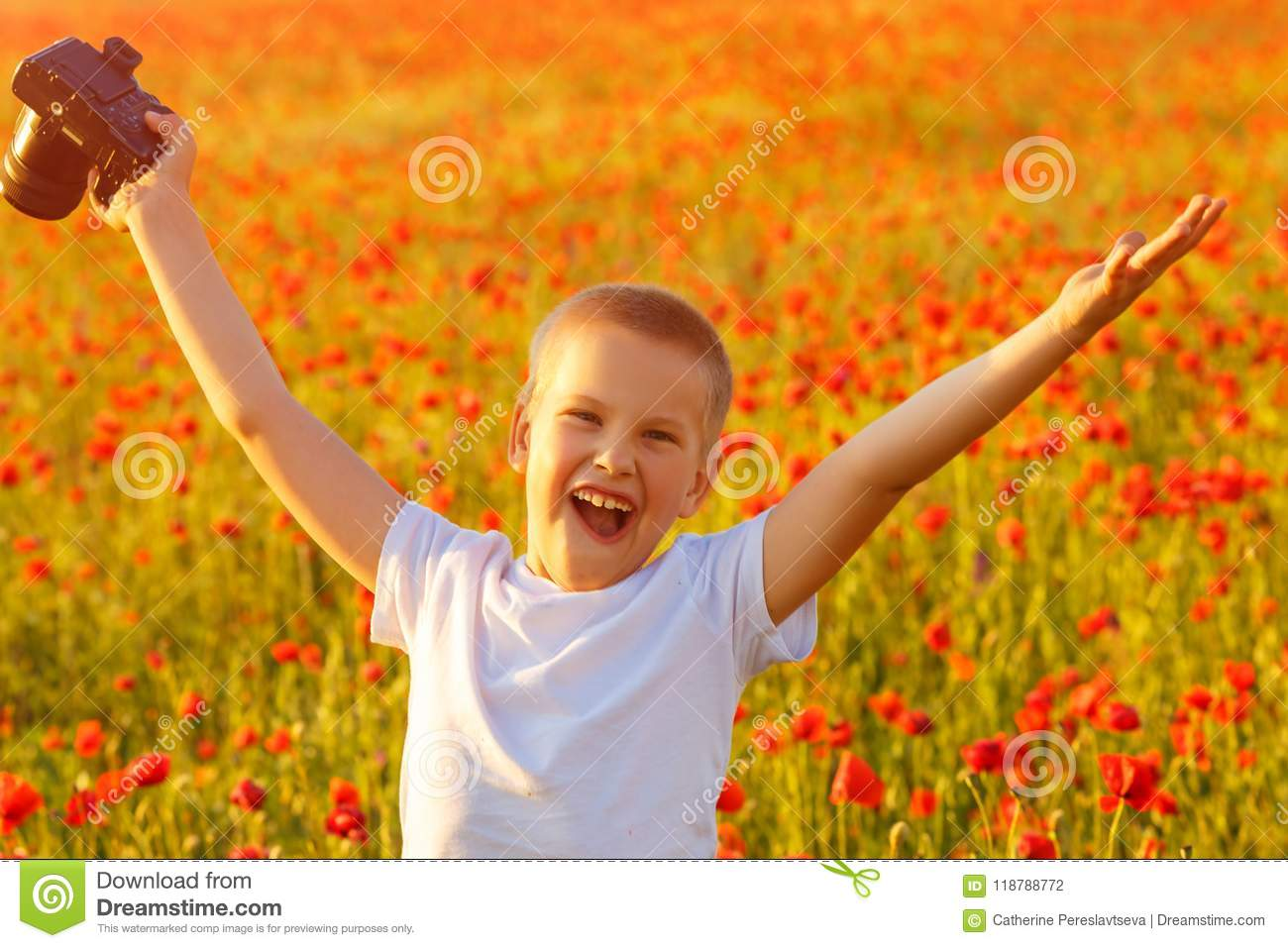 Little happy boy in poppy field at sunset with camera