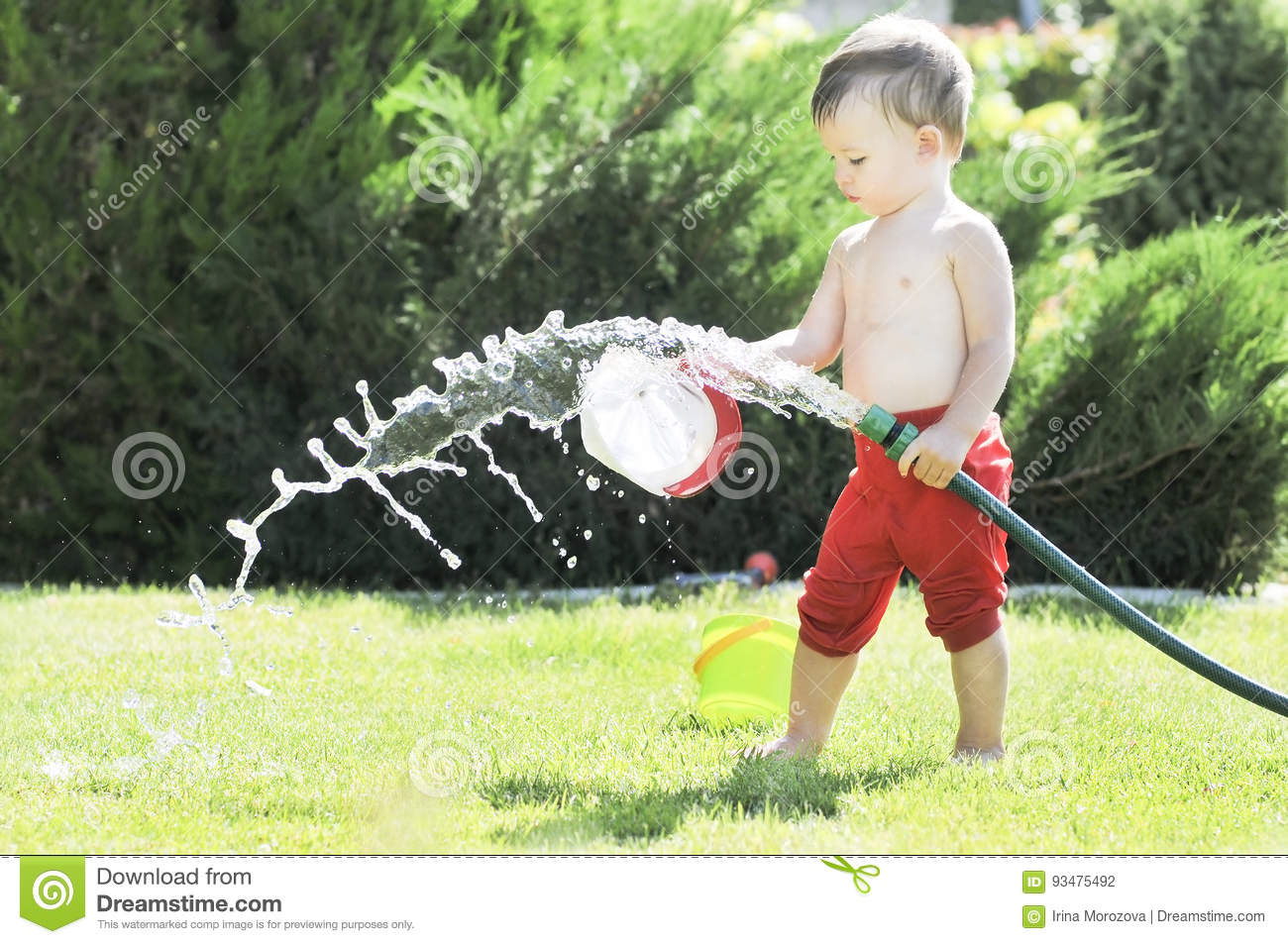 Little boy pours from a hose in the garden on a hot summer day on a green lawn, splashing water