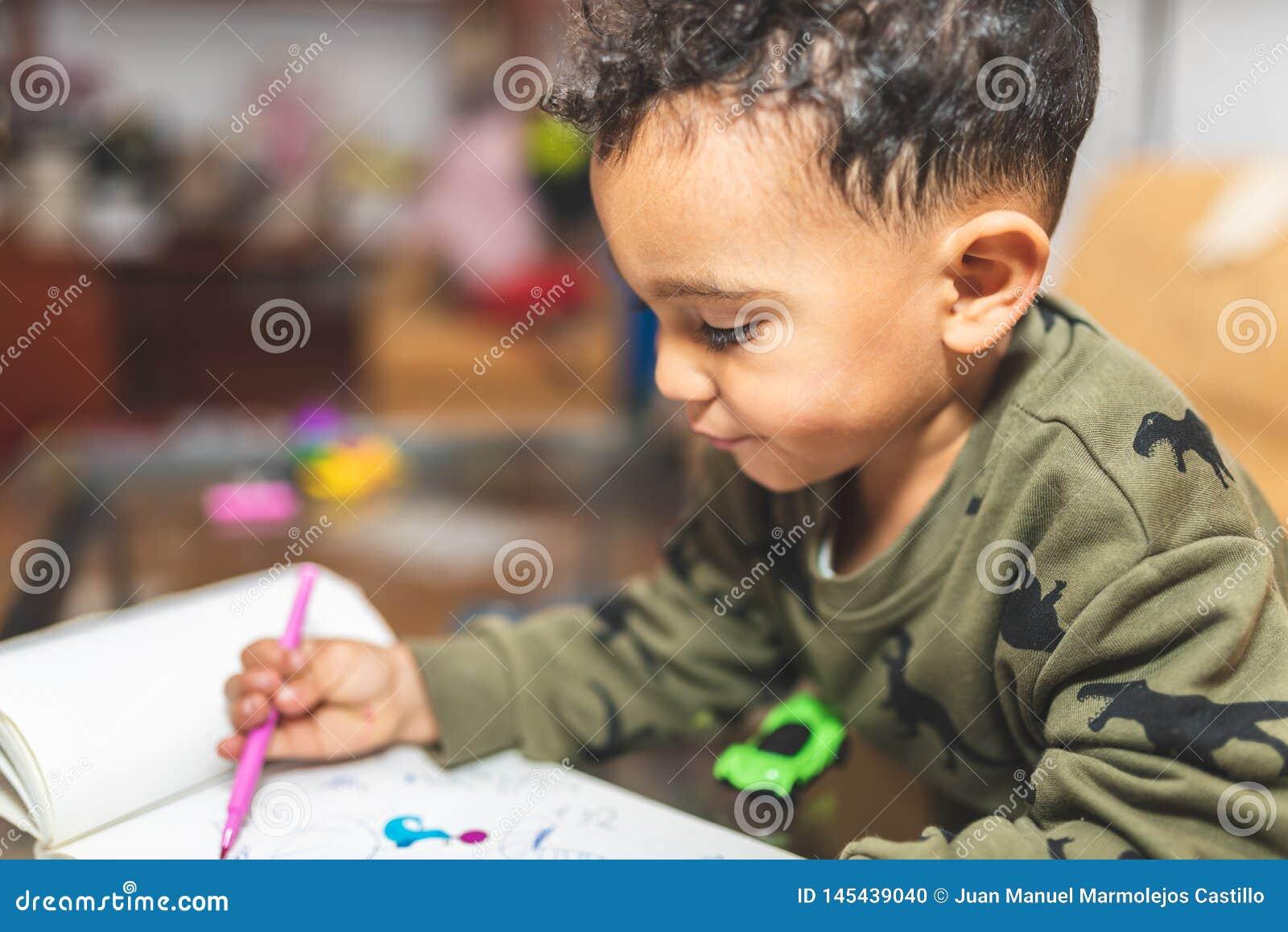 Little Boy que tira em um caderno