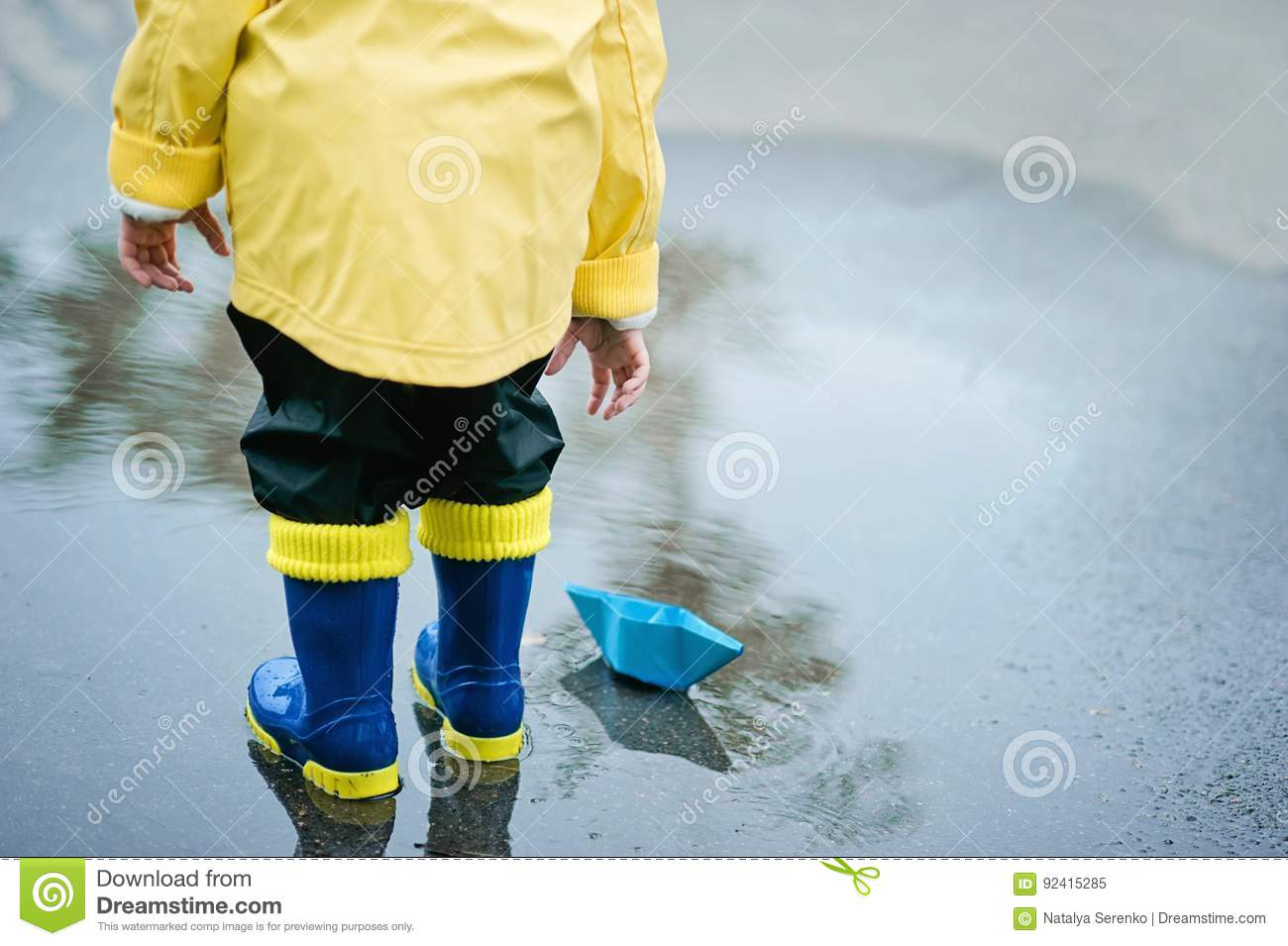 Little boy in raincoat and rubber boots playing in puddle. Happy little kid with paper ship