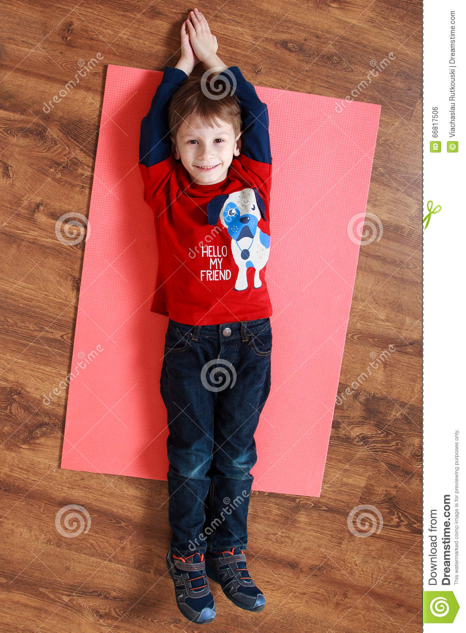 Little Boy In A Red Shirt Is Laying On A Mat , Doing ...