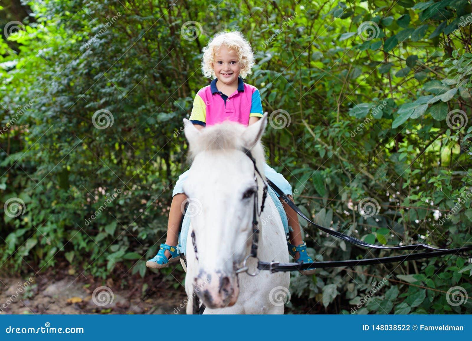 Child riding horse. Kids ride pony