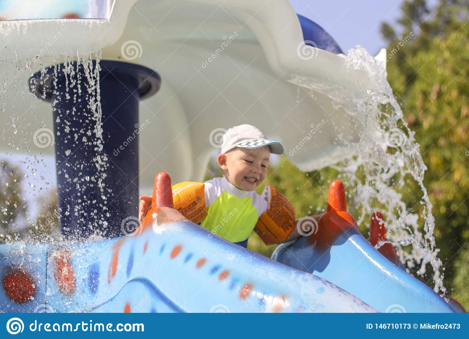 A little boy rolls down a water slide. Children`s joy in the water park. Summer vacation for children in the water park