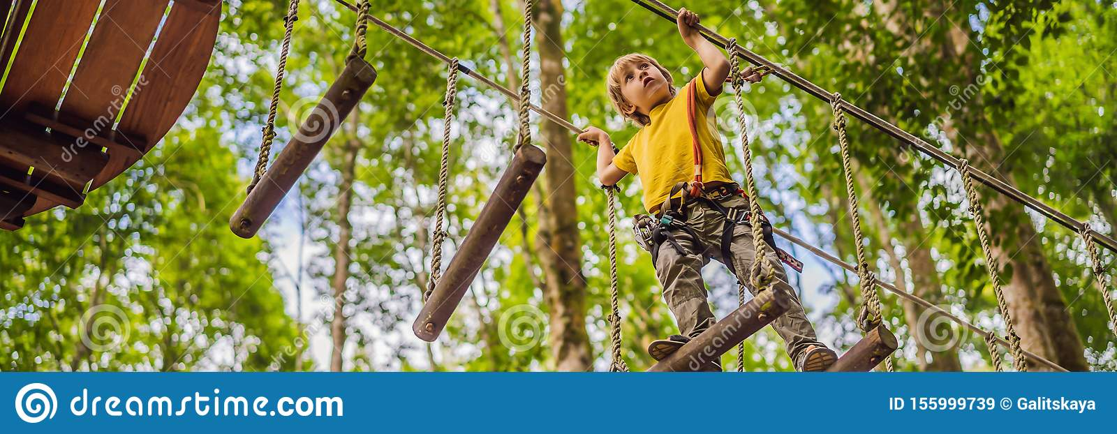 Little boy in a rope park. Active physical recreation of the child in the fresh air in the park. Training for children