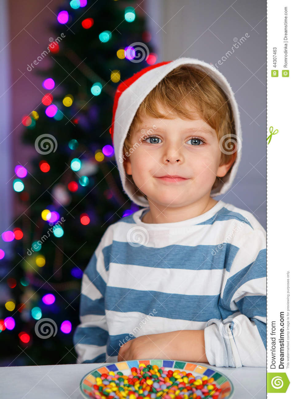 c8fd0fe6e4e Little Boy In Santa Hat With Christmas Tree And Lights Stock Image ...
