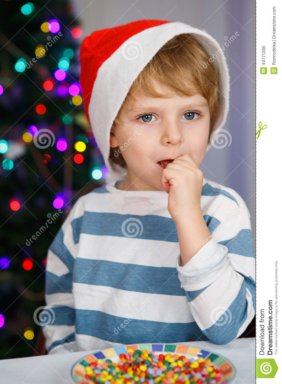 ca94e9da0c2 Little boy in santa hat with christmas tree and lights on background eating  sweets