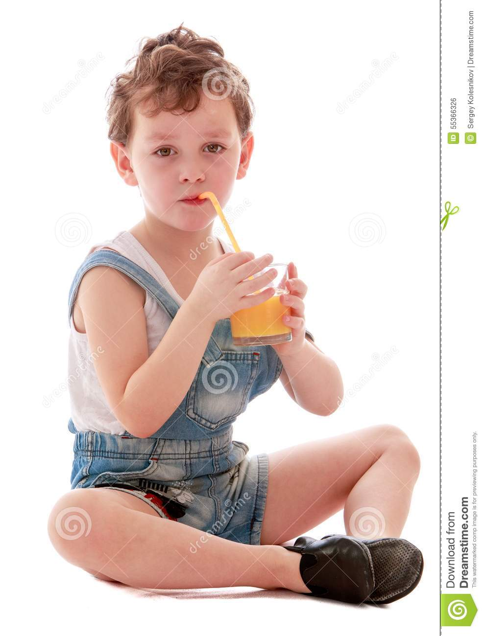 little boy in short denim overalls drinking stock photo