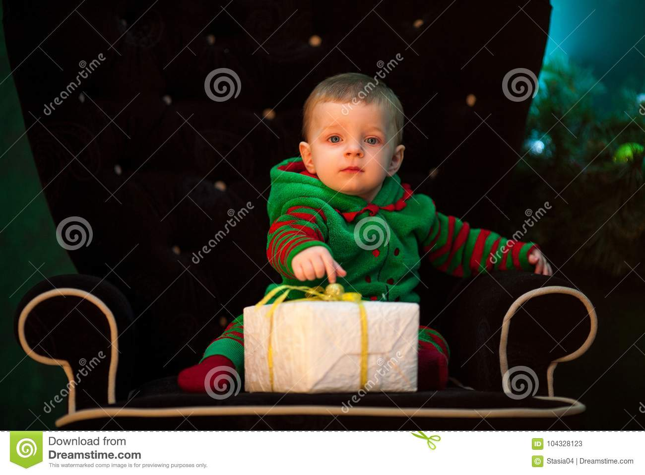Little boy sits in armchair with Christmas gift box.