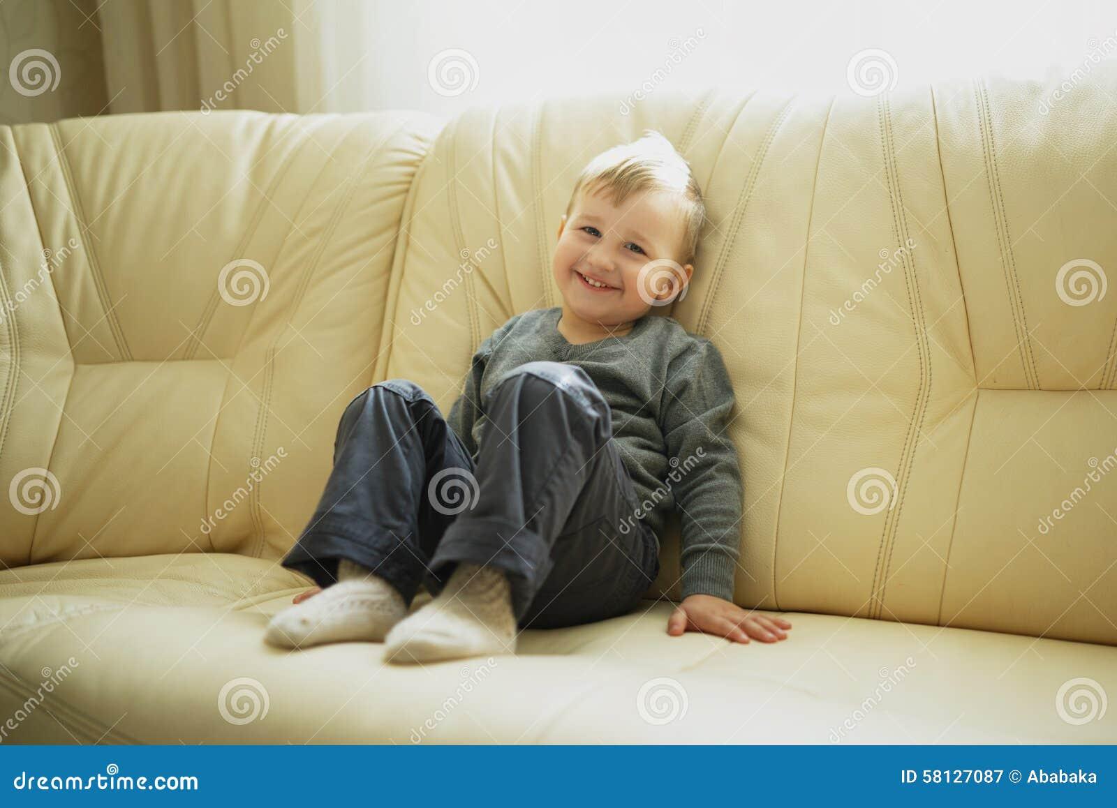 little boy sitting on couch stock image image 58127087. Black Bedroom Furniture Sets. Home Design Ideas