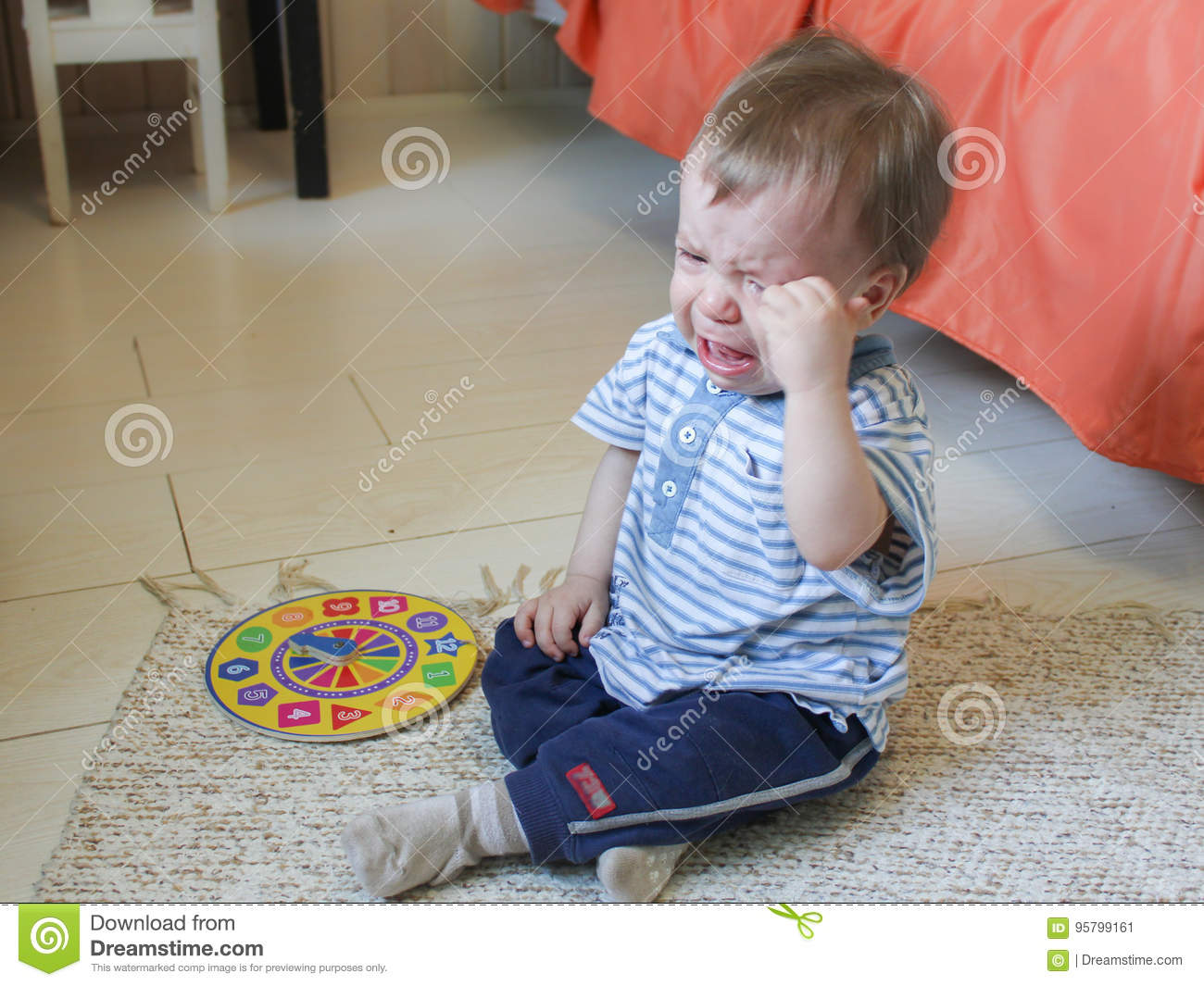 Little boy sitting on the floor, he`s upset and crying. The chil