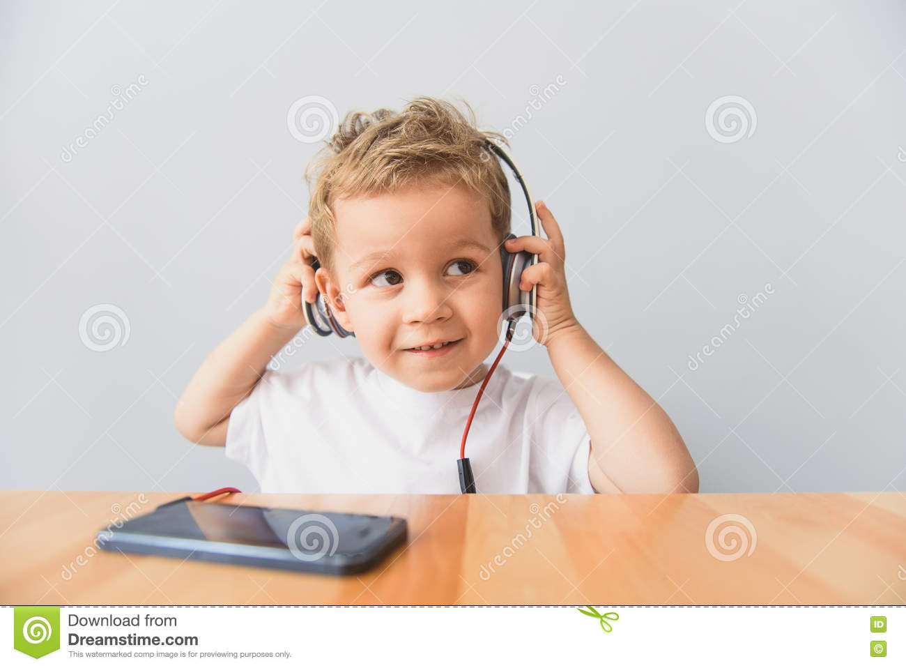 Music is for everyone smiling cute little boy listening to music on headphones using smartphone sitting at desk in studio
