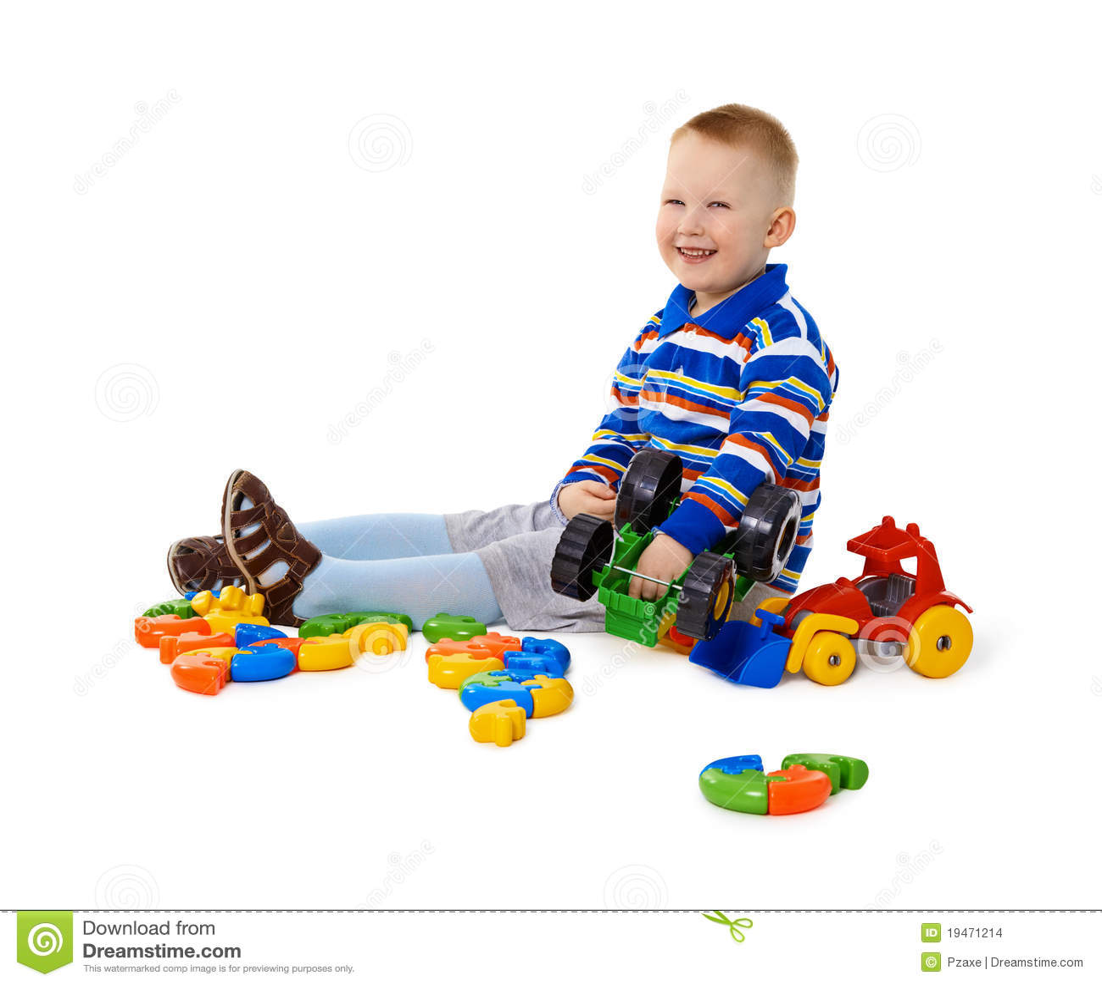 Little Boy Toys : Little boy sitting among toys on floor stock images