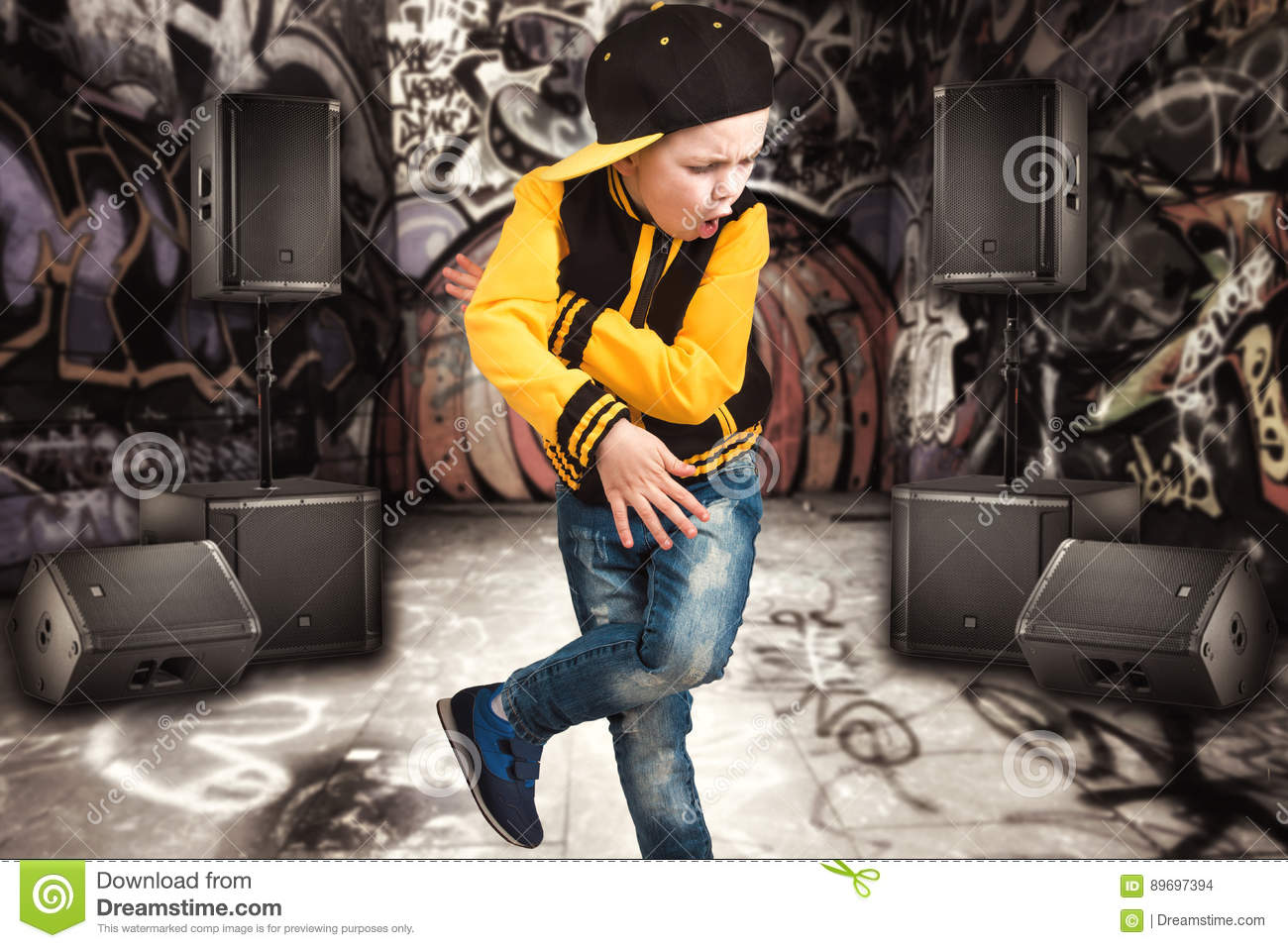 The little boy in the style of Hip-Hop . Children`s fashion.Cap and jacket. The Young Rapper.Graffiti on the walls.Cool rap dj.