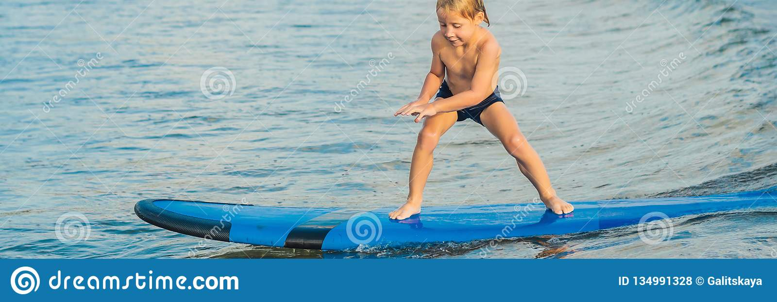 Little boy surfing on tropical beach. Child on surf board on ocean wave. Active water sports for kids. Kid swimming with