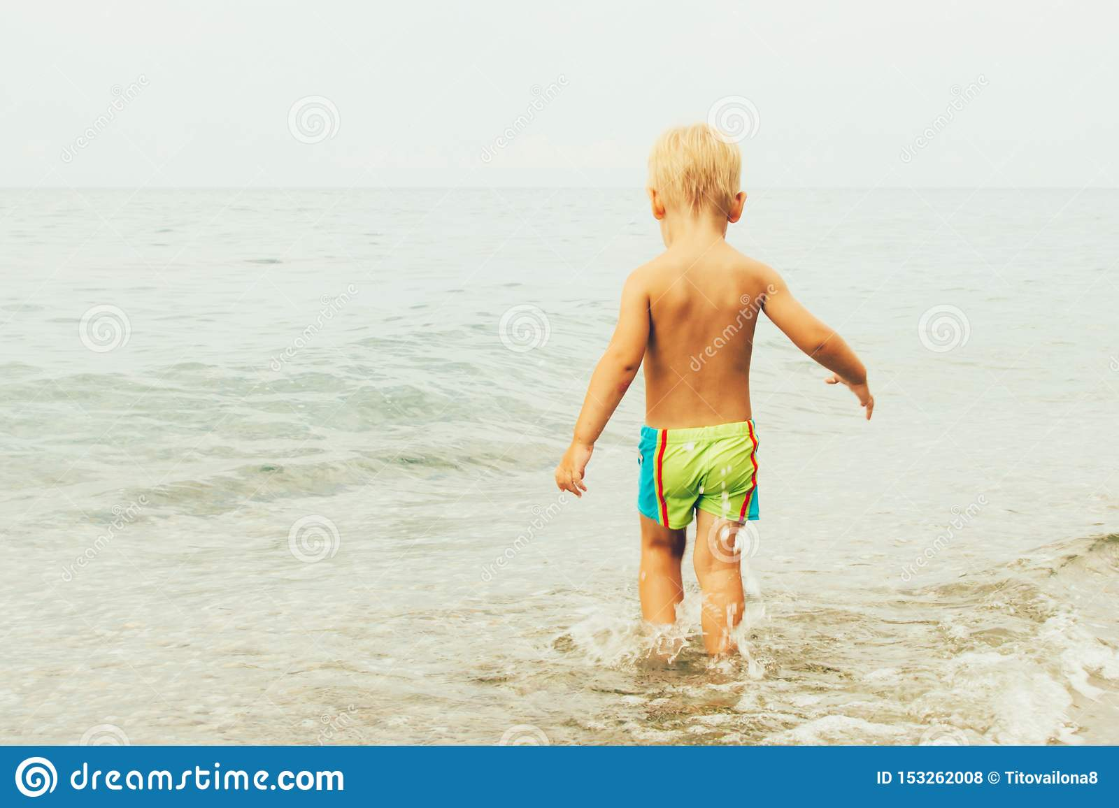 A little boy in swimming trunks comes into the sea, the view from the back. Summer concept of vacation and innocence.