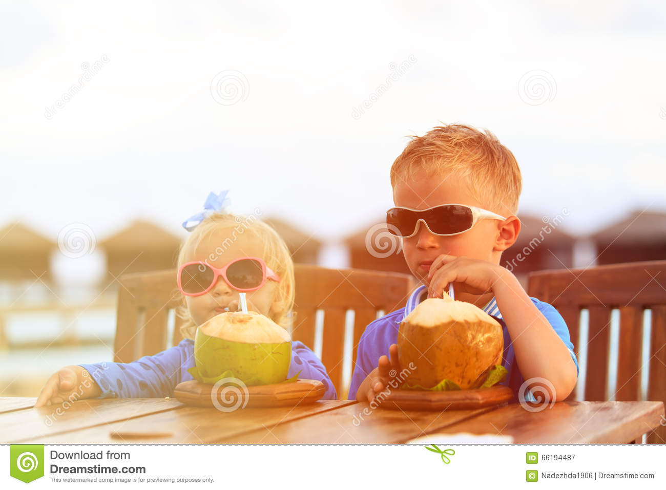 Little boy and toddler girl drinking coconut cocktail on beach