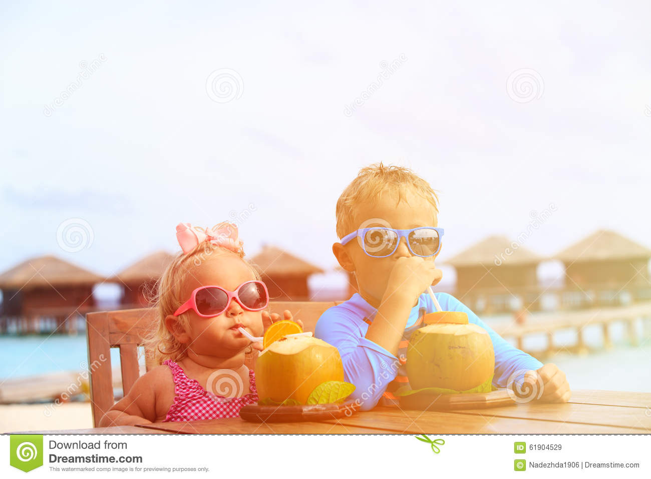 Little boy and toddler girl drinking coconut
