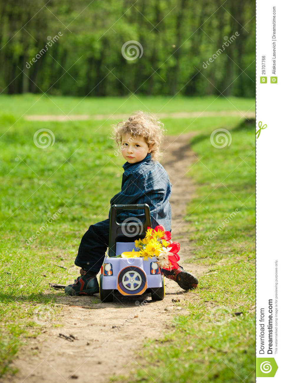 Little Boy With Toy Car : Little boy on a toy car in park royalty free stock image