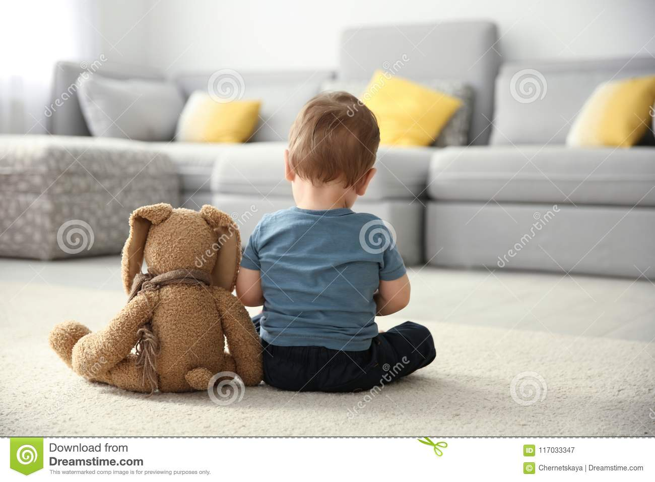 Little boy with toy sitting on floor in living room.