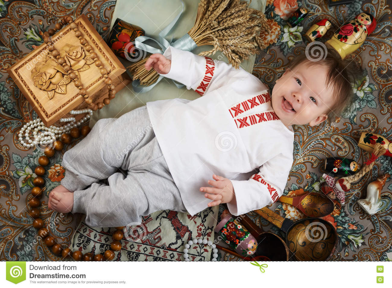 Little boy in a traditional russian shirt surrounded by russian antiques
