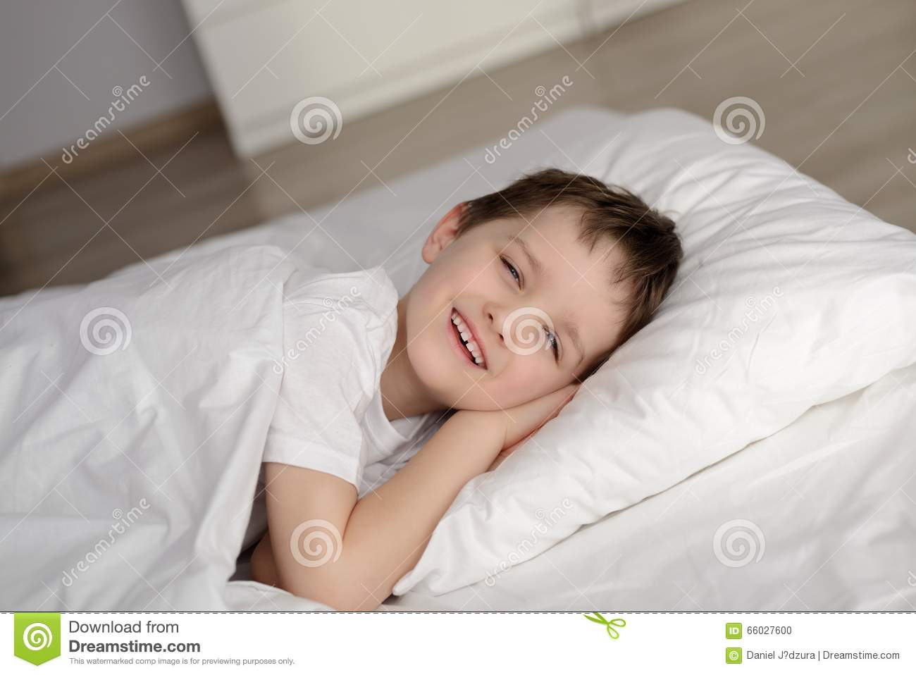 little boy waking up in white bed with eyes open stock photo image 66027600. Black Bedroom Furniture Sets. Home Design Ideas