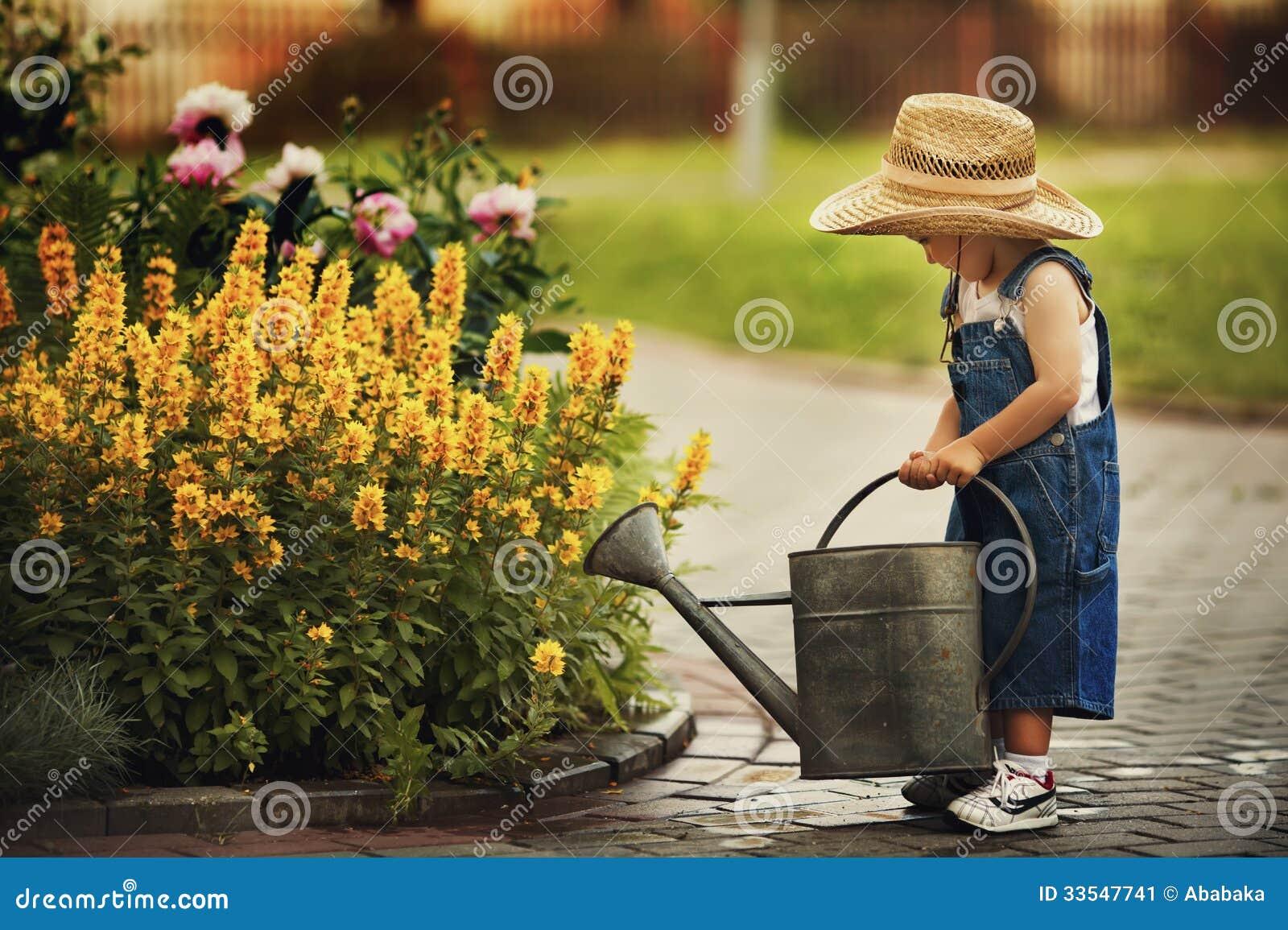Little boy watering flowers