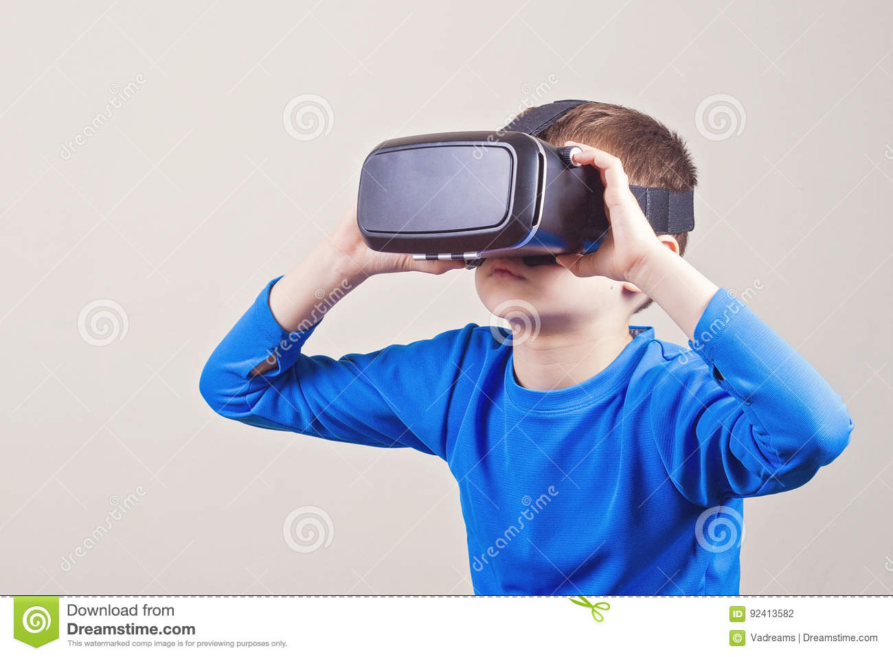 ec4d7c5cdb71 Little kid wearing virtual reality VR goggles watching movies or playing  video games