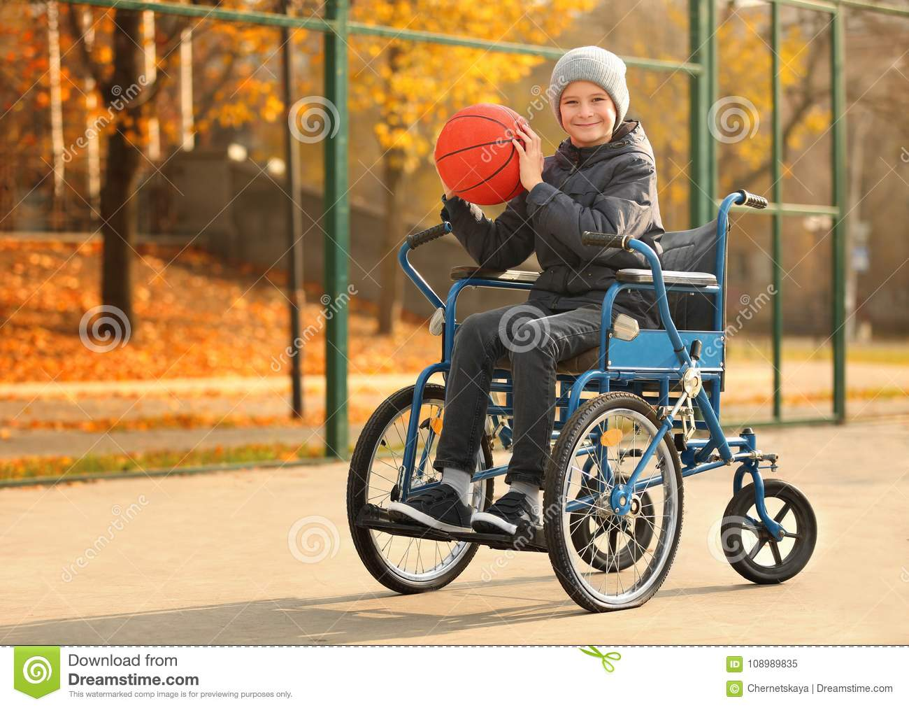 Little boy in wheelchair with ball