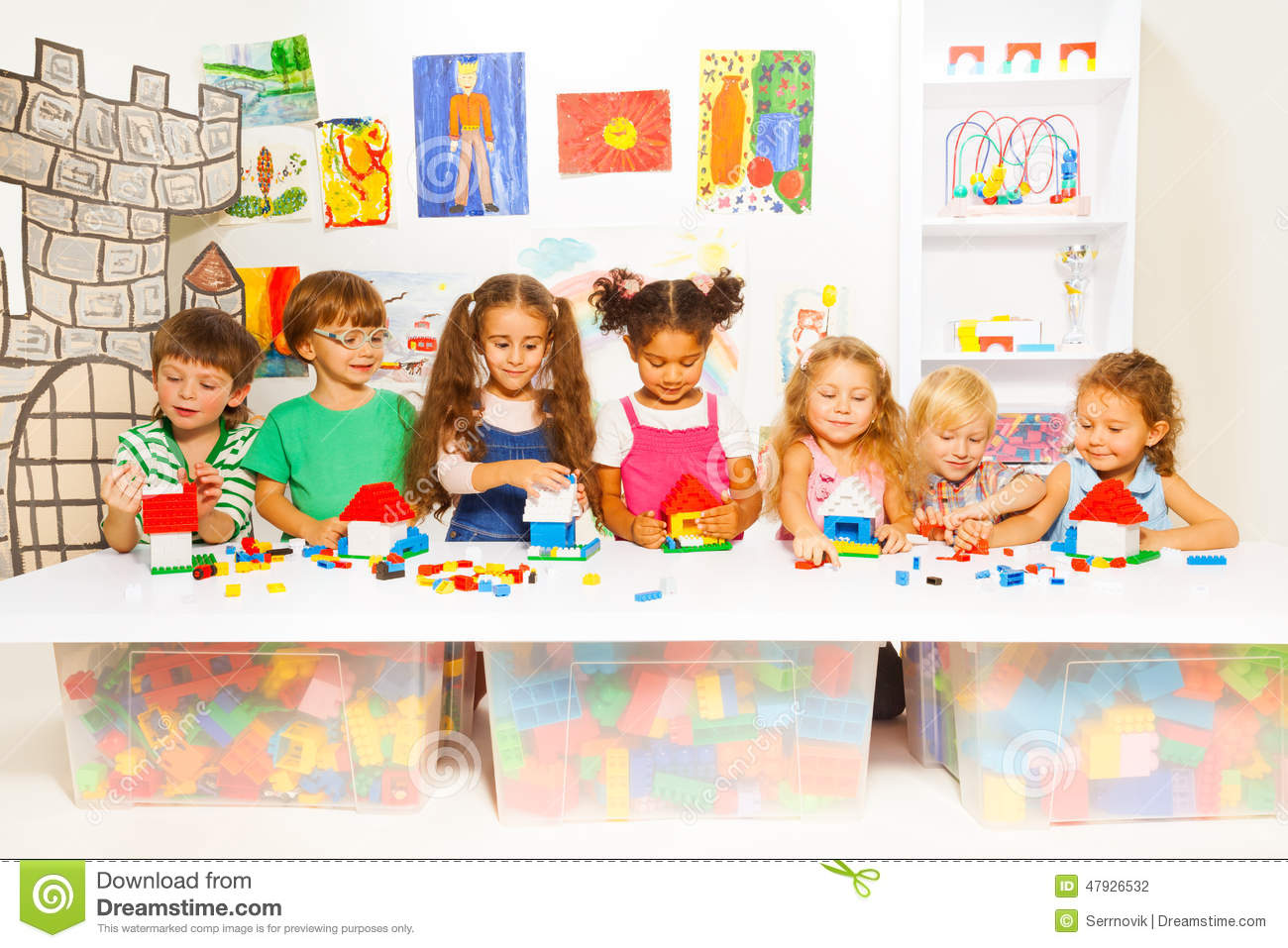 Kinder Garden: Little Boys And Girls Constructing Toy Houses Stock Photo
