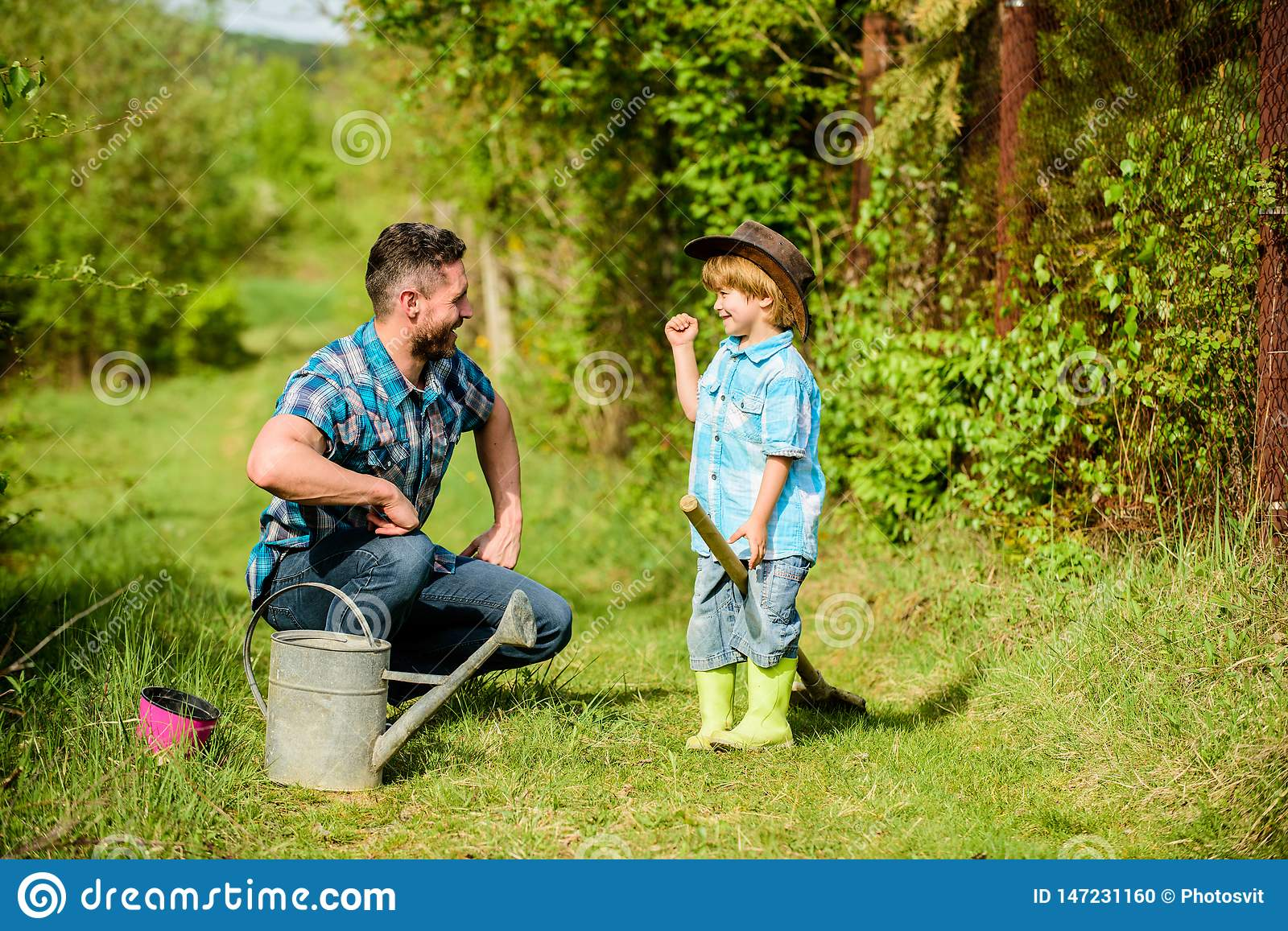 Little break. happy earth day. Family tree nursering. father and son in cowboy hat on ranch. watering can, pot and