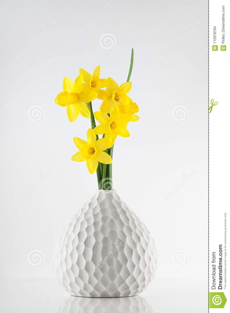Little bright yellow Daffodils in a vase on white kitchen table