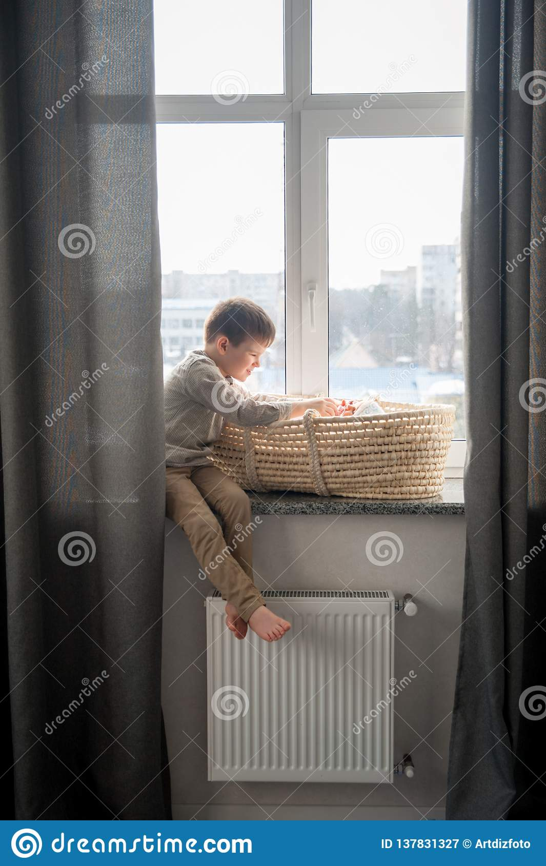 Little brother is sitting near the window with himnewborn sister in the cradle. Children with small age difference